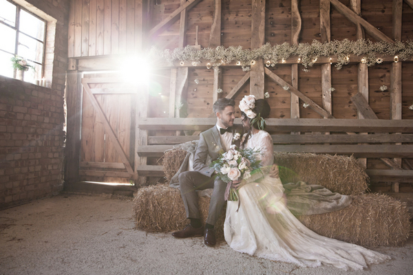 Bride and groom sitting on hay bale in barn