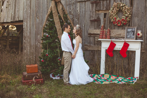 Bride and groom holding hands in front of Christmas tree