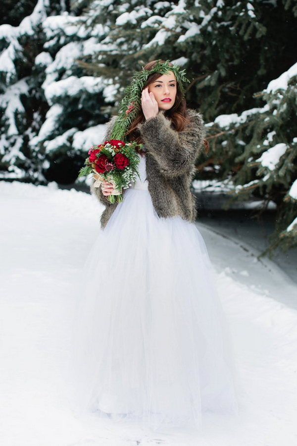 Bride with fur shrug standing in snow