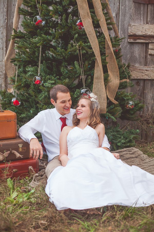 Bride and groom sitting in front of Christmas tree