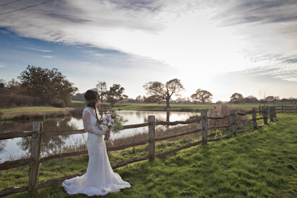 Bride leaning on fence in countryside