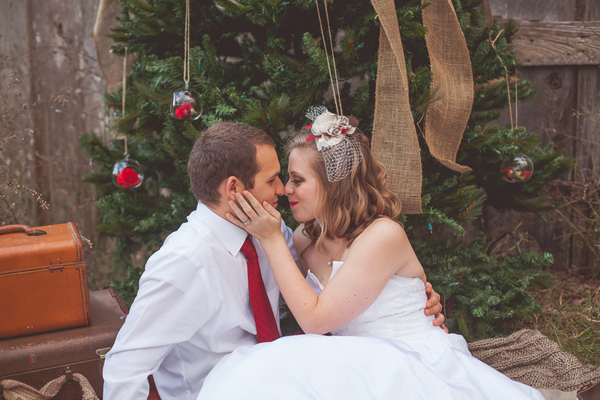 Bride and groom about to kiss in front of Christmas tree