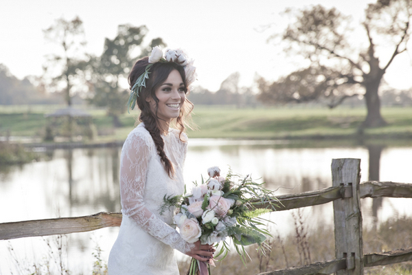 Bride holding bouquet in front of pond