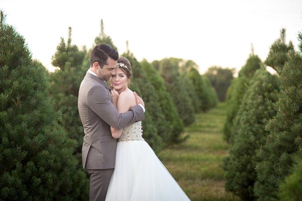 Groom hugging bride on Christmas tree farm