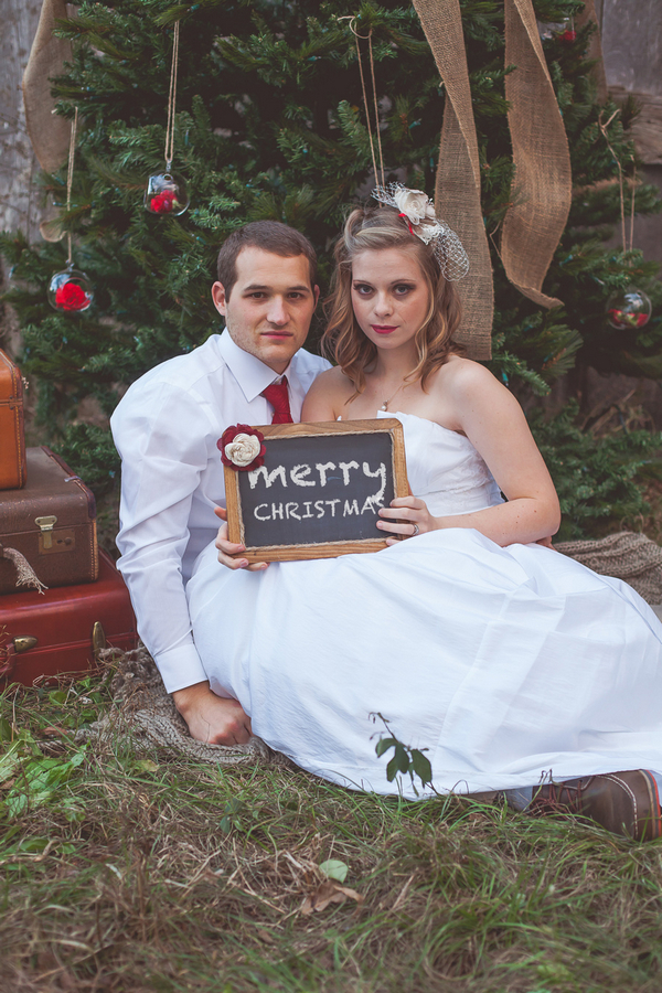 Bride and groom holding merry Christmas sign