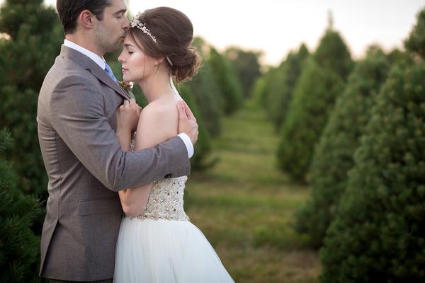 Groom kissing bride on head on Christmas tree farm