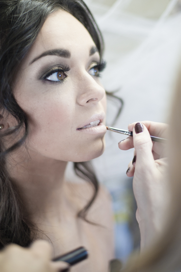 Bride having lip gloss applied