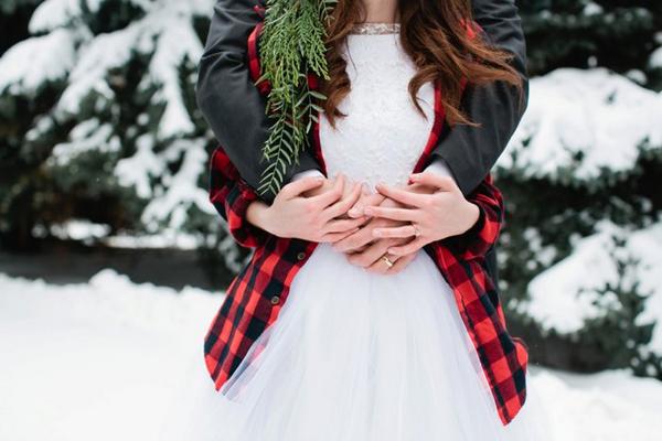 Groom with arms around bride's waist