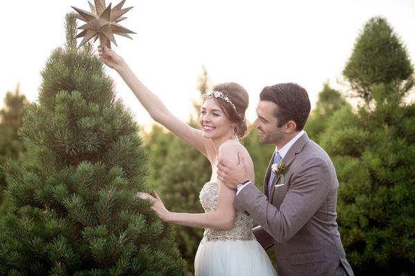 Groom standing behind bride putting star on Christmas tree