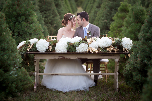 Bride and groom sitting at table on Christmas tree farm