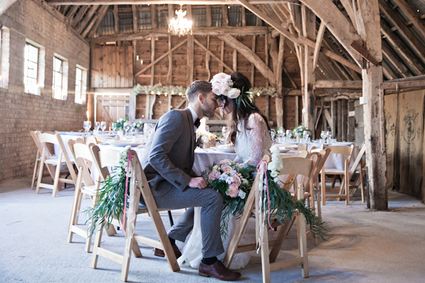 Bride and groom sitting at table in barn