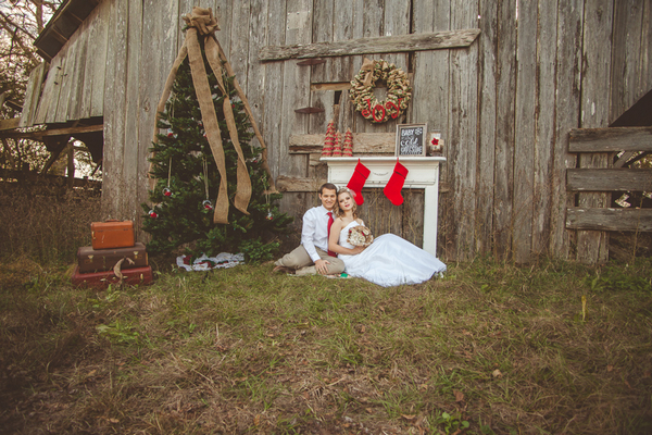 Bride and groom sitting in front of mantelpiece and Christmas tree