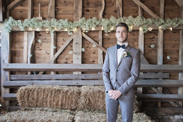 Groom standing in barn