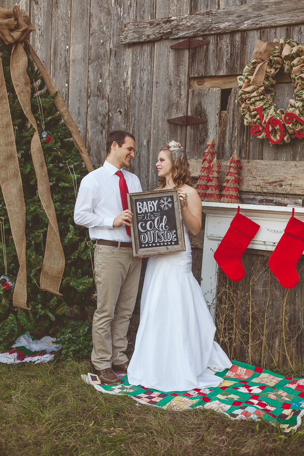 Bride and groom holding 'Baby It's Cold Outside' sign