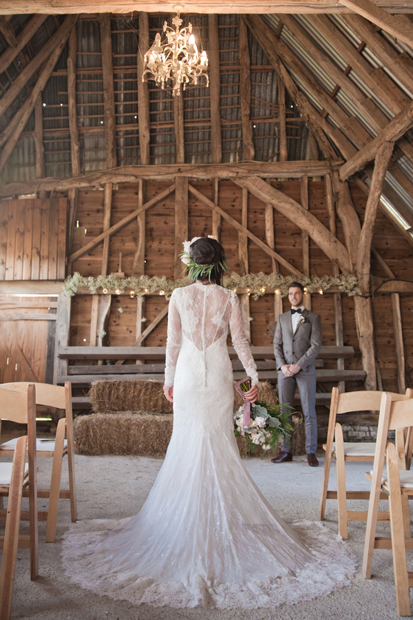 Bride in barn looking at groom