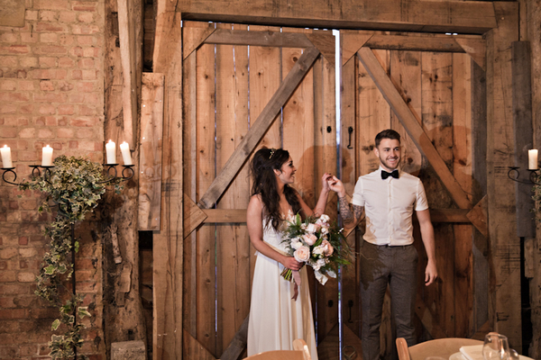 Bride and groom by barn door
