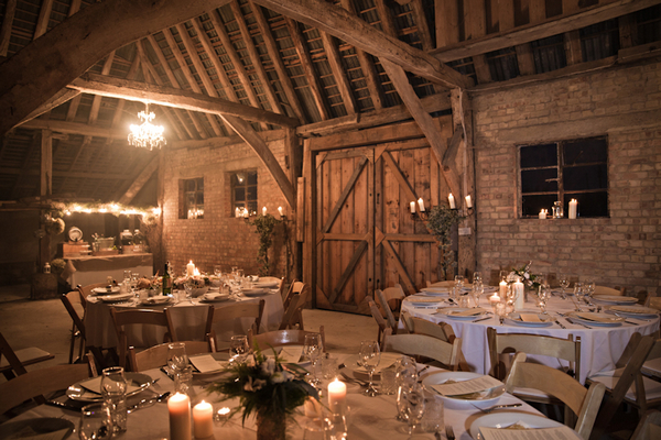 Wedding tables in barn lit up by candlelight
