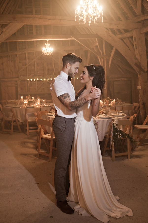 Bride and groom dance in barn