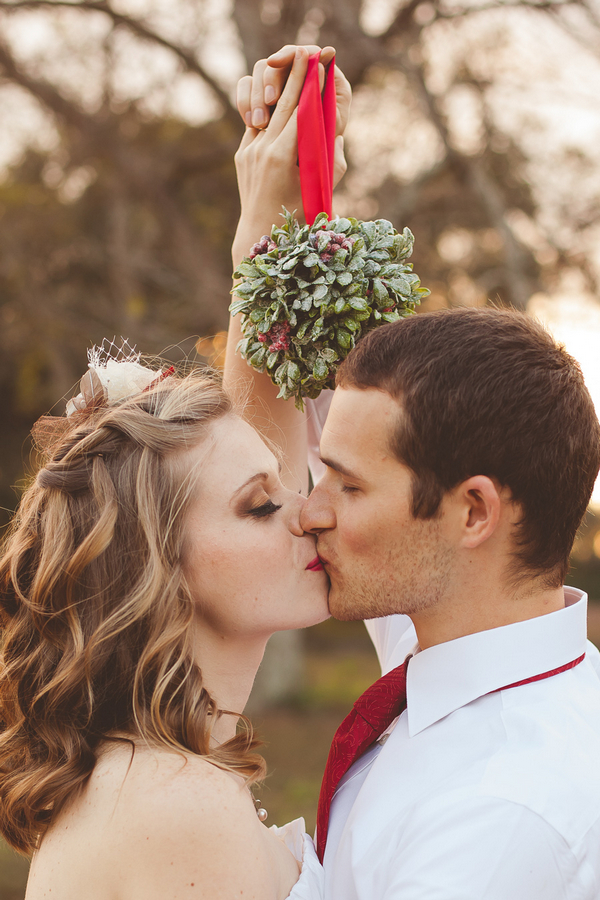 Bride and groom kissing under mistletoe