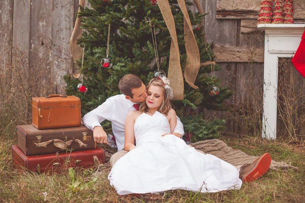 Groom kissing bride on cheek sitting in front of Christmas tree