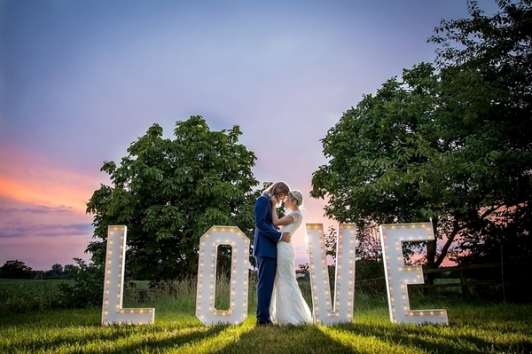 Bride and groom standing in front of large LOVE letters in field - Picture by Katherine Ashdown Photography