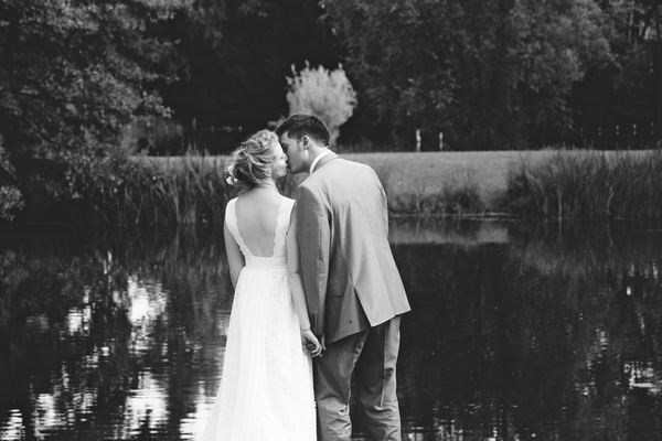 Bride and groom kissing by lake