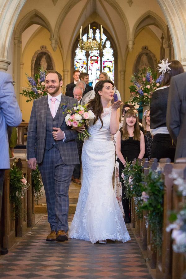 Bride blowing kiss as she leaves church