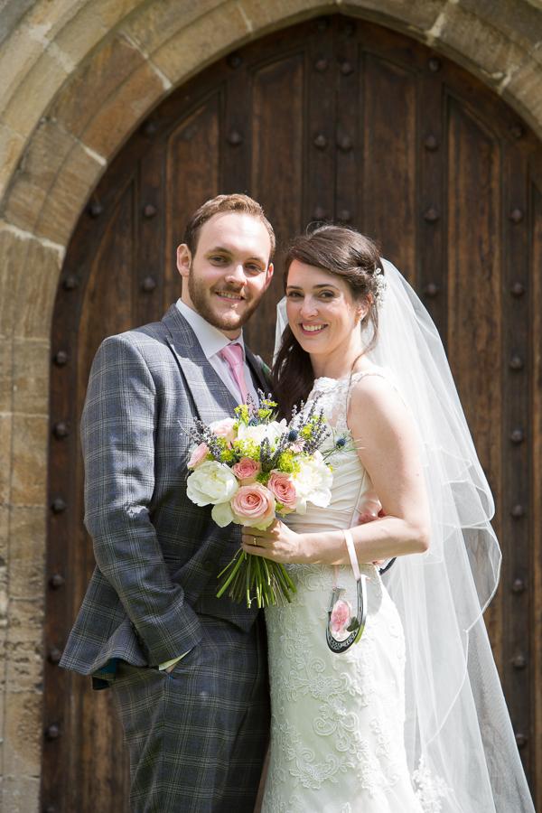 Bride and groom posing by church door