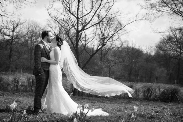 Bride and groom kissing with bride's veil blowing in wind