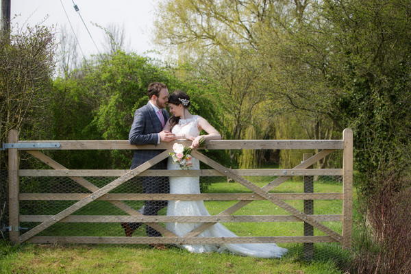 Bride and groom leaning against gate