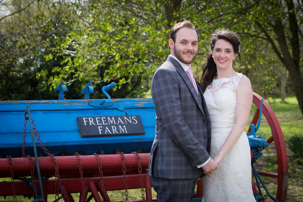 Bride and groom next to farm machinery
