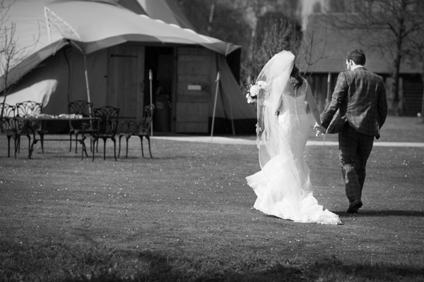 Bride and groom walking to tipi