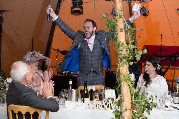 Groom with arms in the air