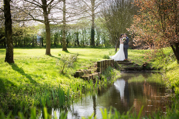 Bride and groom standing by pond