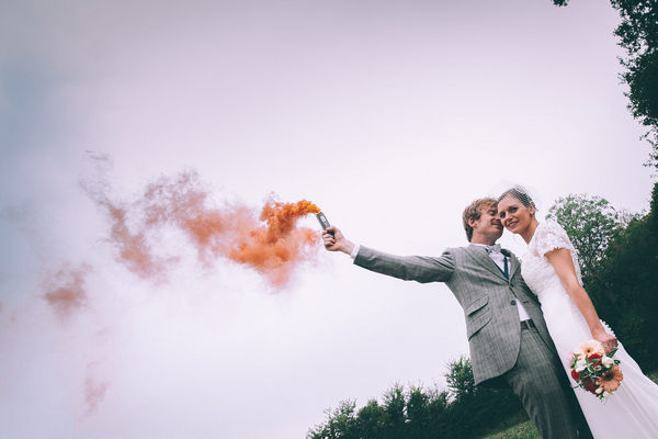 Groom standing with bride holding up a flare
