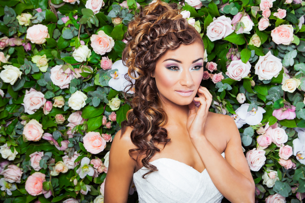 Bride with hand on face standing in front of flower wall