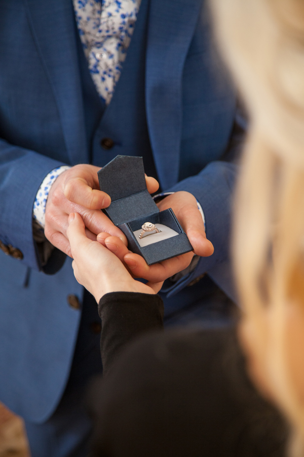 Man holding out engagement ring