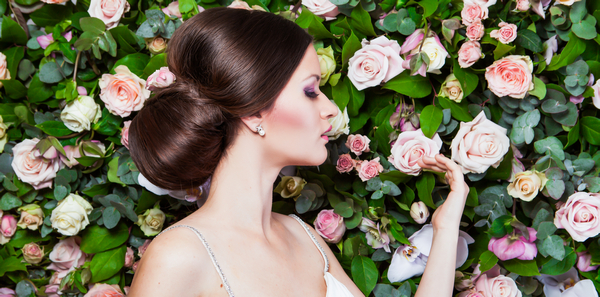 Bride touching flower on flower wall