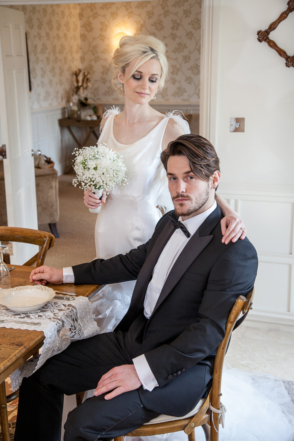 Groom sitting at table with bride standing