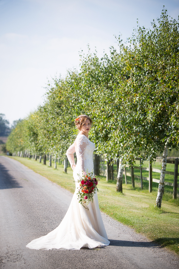 Bride standing in road holding bouquet