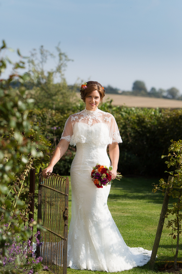 Bride standing by gate holding bouquet