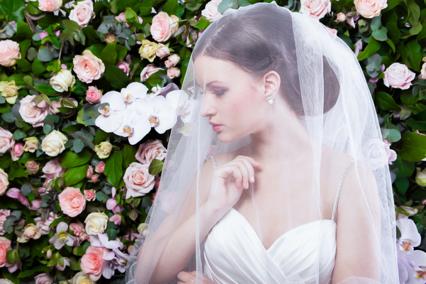 Bride with veil in front of flower wall