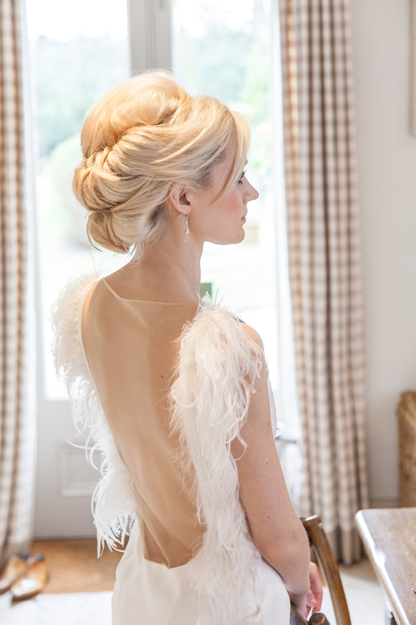 Bride wearing wedding dress with feather detail