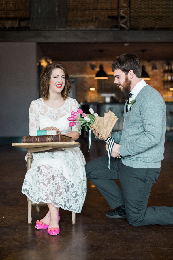 Man giving woman flowers at desk