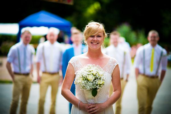 Bride standing in front of groomsmen