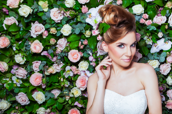 Bride standing in front of flower wall
