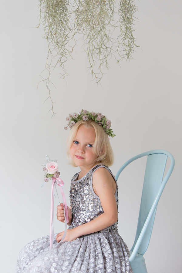 Flower girl sitting on a chair holding a rose star wand