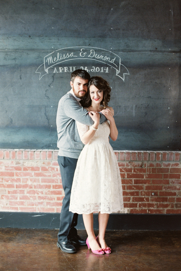 Couple in front of wedding sign written on chalkboard