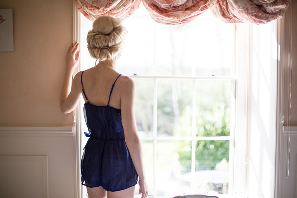Woman in lingerie looking out of window