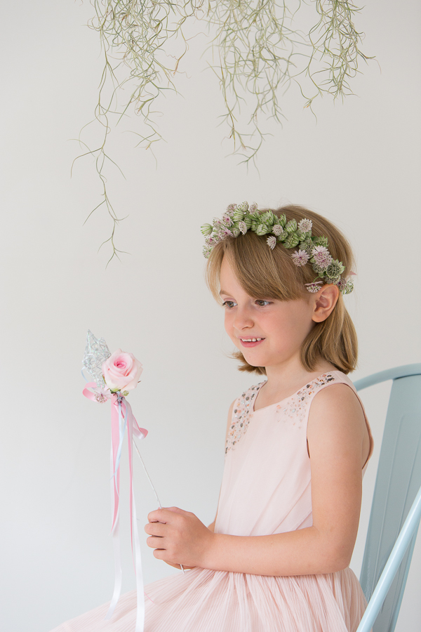 Flower girl sitting holding a rose star wand